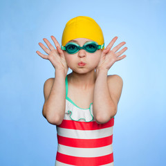 """Studio portrait of girl (10-11) wearing swimsuit, swimming cap and swimming goggles"""