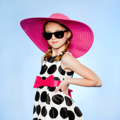 """Studio portrait of elegant girl (10-11) wearing hat, sunglasses and dress"""