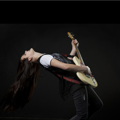 Studio shot of teenage girl (14-15) playing electric guitar