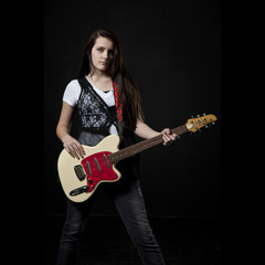 Studio portrait of teenage girl (14-15) with electric guitar