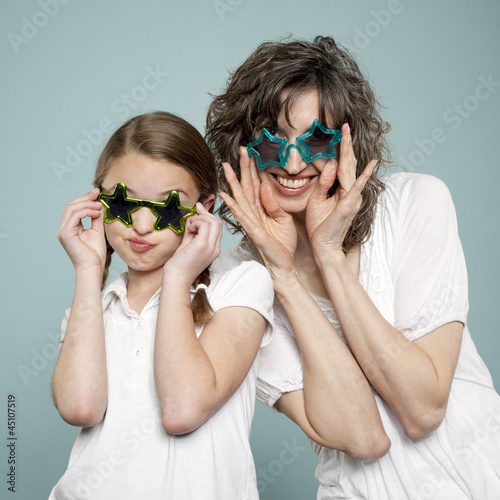 Studio shot of mother and daughter (10-11) wearing star shaped sunglasses