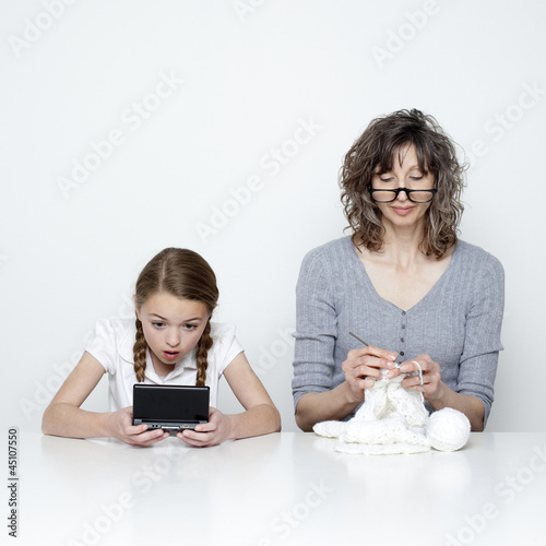 Studio shot of mother knitting and daughter (10-11) using handheld video game