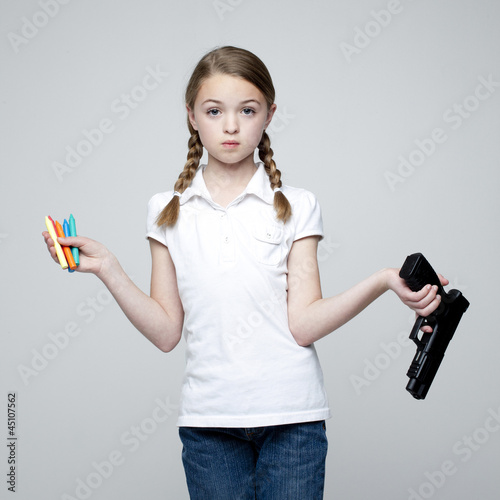 Studio shot of girl (10-11) holding handgun and crayons