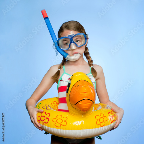 Studio shot of girl (10-11) with snorkeling gear and inflatable ring