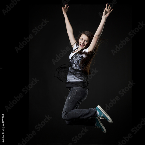 Studio shot of teenage girl (14-15) jumping