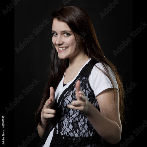 Studio portrait of teenage girl (14-15) pointing to camera