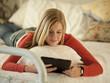 """USA, Utah, Cedar Hills, Teenage girl (14-15) lying on bed, using digital tablet"""