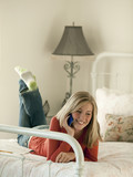 """USA, Utah, Cedar Hills, Teenage girl (14-15) lying on bed, talking on mobile phone"""