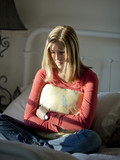 """USA, Utah, Cedar Hills, Sad teenage girl sitting on bed, embracing pillow"""
