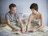 couple playing cards in bed