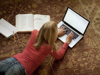 """USA, Utah, Cedar Hills, Teenage girl (14-15) lying on floor, using laptop"""