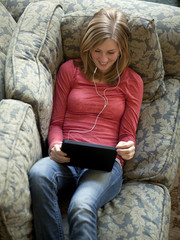 """USA, Utah, Cedar Hills, Teenage girl (14-15) lying on listening to music from using digital tablet"""