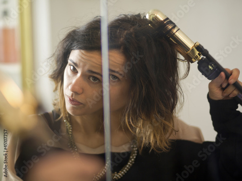 """USA, Utah, Provo, Young woman using curler in front of mirror"""