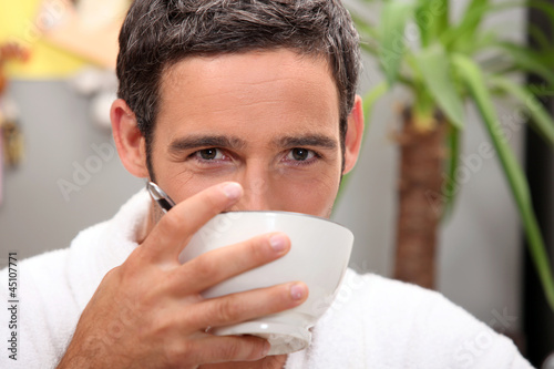 Black man drinking from bowl