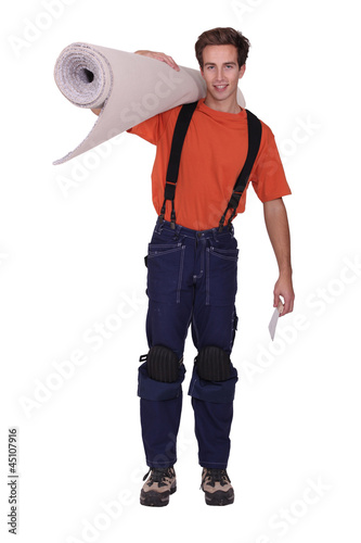 Man carrying roll of carpet over shoulder