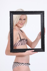 Woman in her undies holding up a picture frame