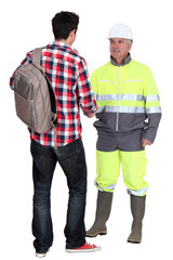 Builder greeting young trainee