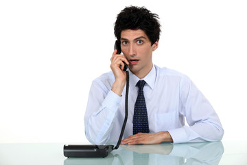 Shocked office worker sat with telephone