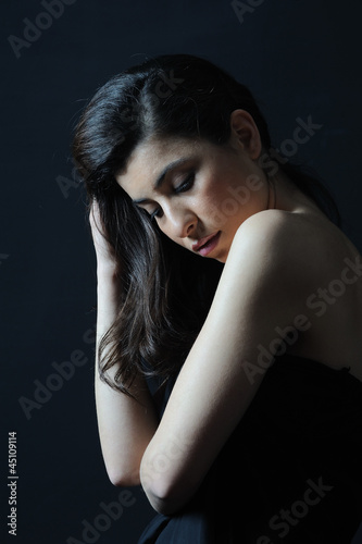 Lonely girl isolated black background