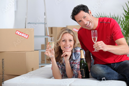 Couple holding champagne glasses boxes in background