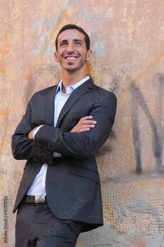 Middle-east businessman standing near a wall and smiling