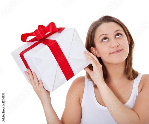 Mädchen schüttelt sanft ein Geschenk