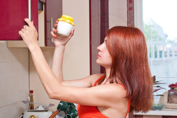 beautiful sexy young woman getting out of cupboard a jar