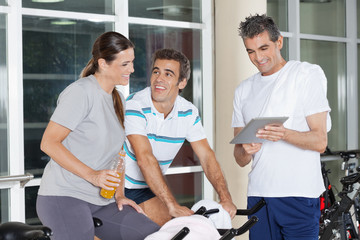 Friends Using Digital Tablet In Gym