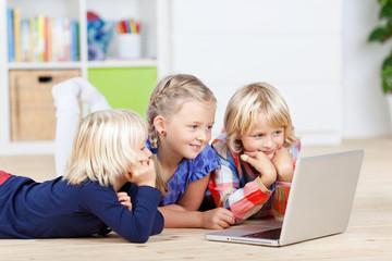 drei mädchen mit laptop im kinderzimmer