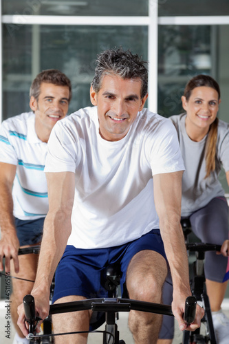 Three People On Exercise Bikes