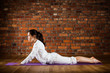 Woman exercising yoga against brick wall