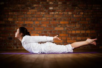 Woman exercising yoga against brick wall