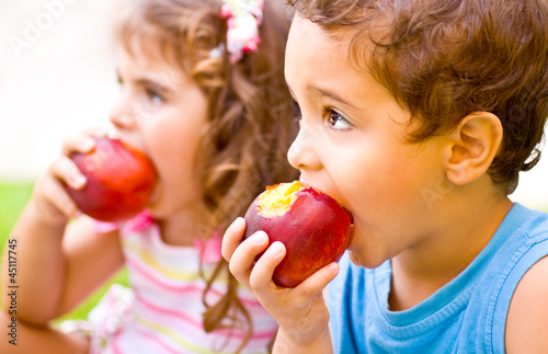 Happy children eating apple