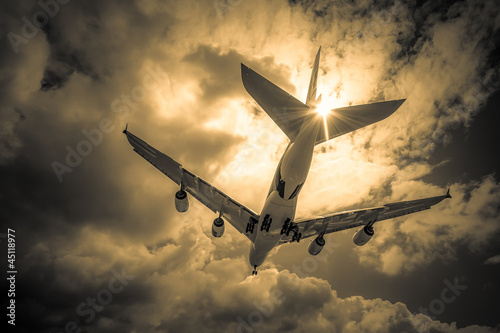 passenger jet landing through golden clouds