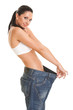 Pretty woman shows her weight loss by wearing an old jeans, isol