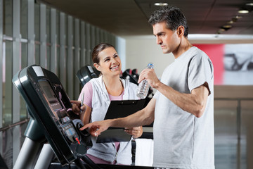 Instructor Looking At Male Client On Treadmill