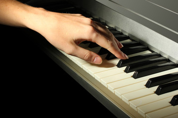 hand of woman playing piano