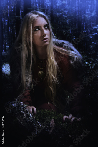 Scandinavian girl in the night forest