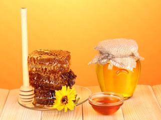 Jar of honey and honeycomb on wooden table on orange background
