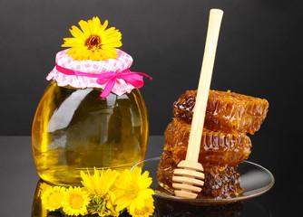 Jar of honey and honeycomb on black background