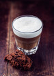 Glass of latte coffee and chocolate cookie on wooden background