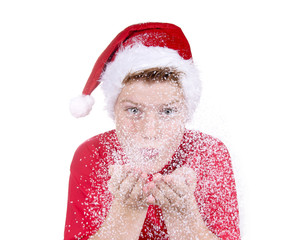 Junge mit Nikolausmütze bläst in Schnee