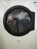 man inside a commercial clothes dryer at a laundromat