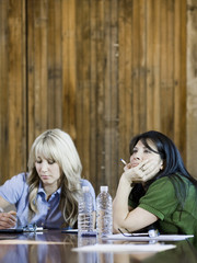 two women bored at a meeting
