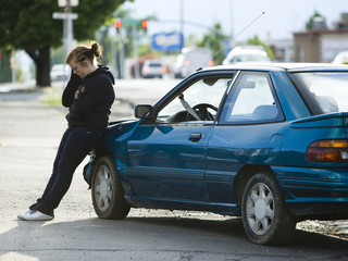 young woman leaning on her car after an accident