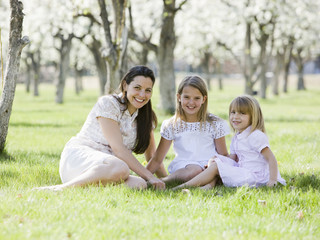 mother and daughters in a blossoming orchard