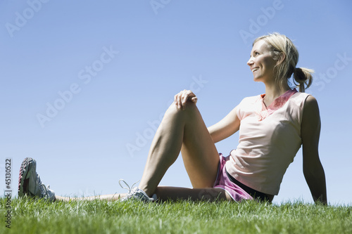 woman sitting on the grass stretching