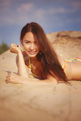 A beautiful girl in a bikini pours sand