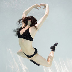 woman swimming underwater in a pool