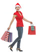 Happy young woman in Christmas hat with shopping bags walking